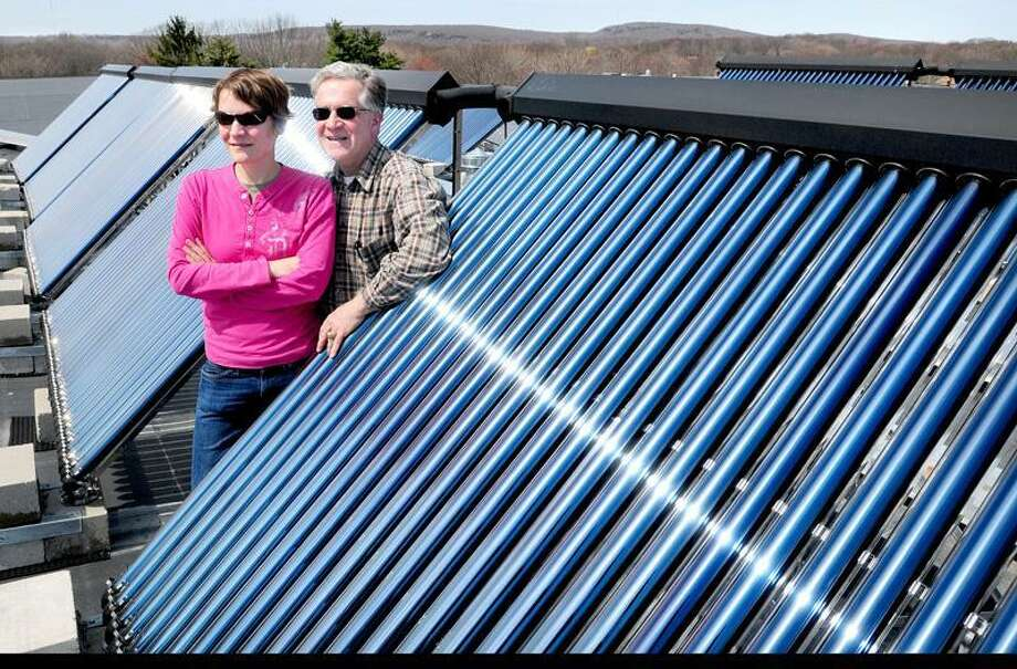 Franklin Enterprises team manager Lauren Tagliatela (left) and her father, Lou Tagliatela Jr., co-owner of Franklin Enterprises, are photographed by an array of solar tubes on the roof of Chestnut Hill South Apartments in Hamden. (Photo by Arnold Gold/New Haven Register)