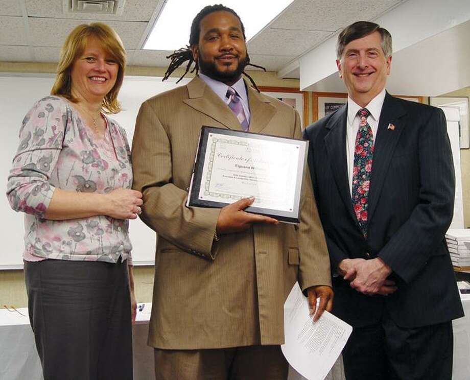"Side Street to Main Street Program 13 graduate Gee Williams, center, is awarded his diploma Monday by Master of Ceremonies Jim Jackson, right, and a representative for the Aetna Foundation during the Side Street to Main Street XIII Graduation Ceremony at the Middletown Chamber of Commerce. The program assists in the development of small, minority-owned businesses in Middlesex County and beyond. Jennifer De Kine, coordinator of the program, is not shown. A total of 14 students graduated from the program Monday. To buy a glossy print of this photo and more, visit <a href=""http://www.middletownpress.com"">www.middletownpress.com</a>. (Sean Connor"