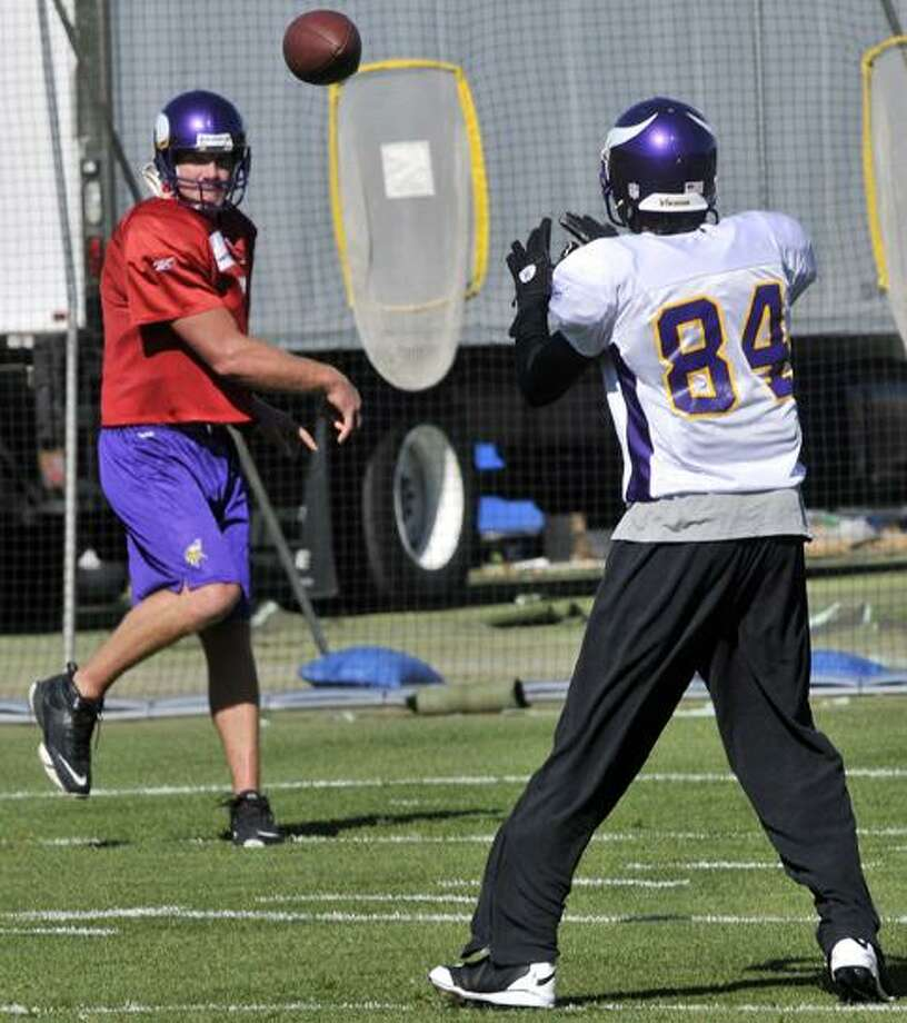 Minnesota Vikings quarterback Brett Favre, left, throws to wide receiver Randy Moss during NFL football practice, Thursday in Eden Prairie, Minn. Moss was traded Wednesday to the Vikings by the New England Patriots. (AP Photo/Jim Mone) Photo: AP / AP