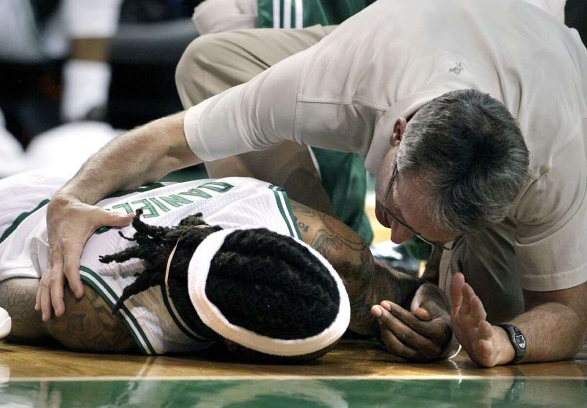 Boston Celtics guard Marquis Daniels is attended to by a trainer after being injured during the first half against the Orlando Magic in an NBA basketball game in Boston on Sunday, Feb. 6, 2011. Daniels was taken off the court on a stretcher. (AP Photo/Elise Amendola)
