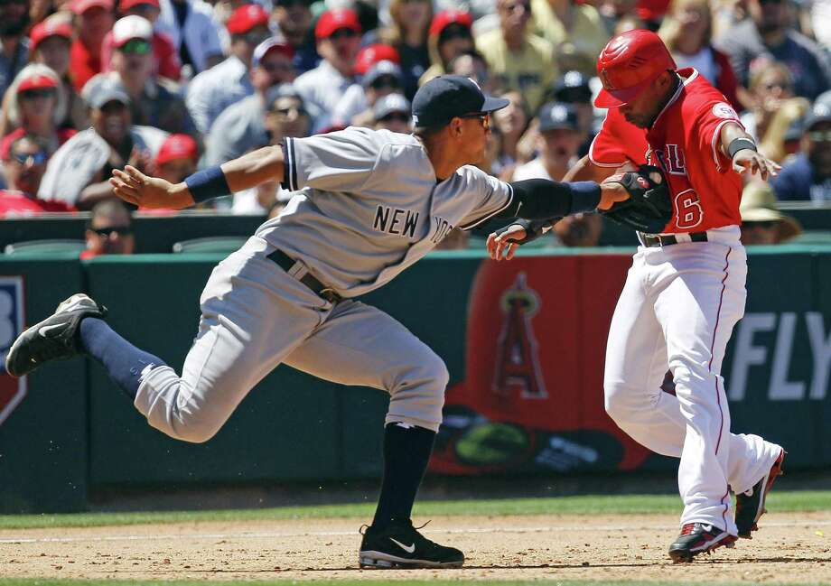 ASSOCIATED PRESS - Los Angeles Angels' Alberto Callaspo, right, is tagged out by New York Yankees third baseman Alex Rodriguez after trying to advance on a ball hit by Mark Trumbo during the sixth inning of a baseball game, Sunday, June 5, 2011, in Anaheim, Calif. Photo: ASSOCIATED PRESS / AP2011