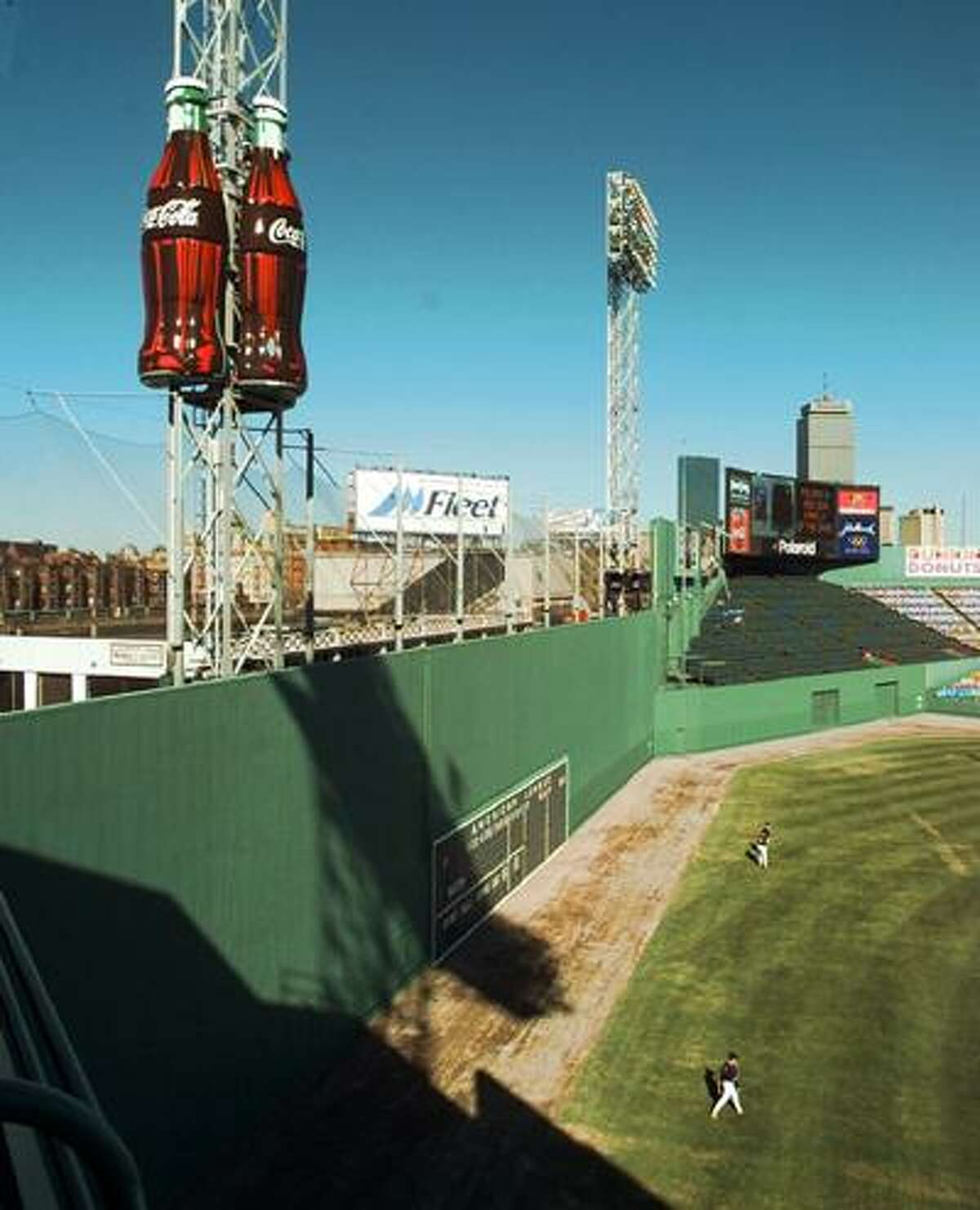 """Twenty-foot high Coca-Cola bottles are seen perched above Fenway Park's famous """"Green Monster"""" Thursday, April 11, 1997 as Boston Red Sox practice below. (AP)"""