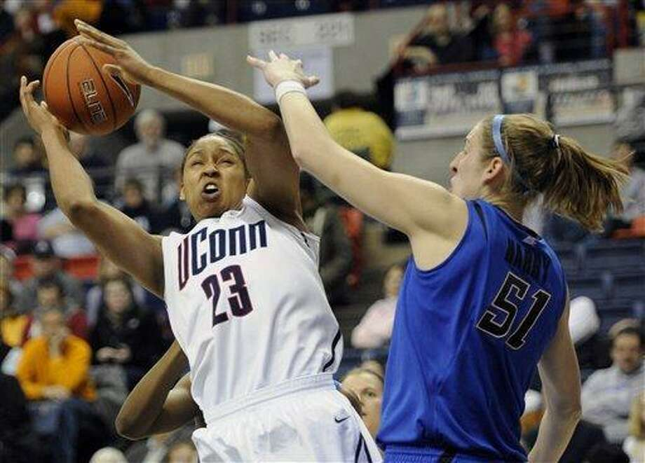Connecticut's Maya Moore, left, is fouled by DePaul's Katherine Harry during Saturday's game. Moore finished with 34 points and 11 rebounds as the Huskies beat the Blue Demons 89-66. Photo: AP / AP2011