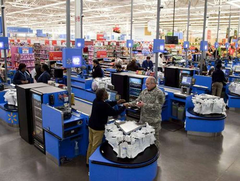 In this photo taken Dec. 15, 2010, the check-out inside a Wal-Mart store in Alexandria, Va., is shown. The battleground for the biggest fight in retailing today is being played out along this suburban highway. Going head-to-head: Wal-Mart against everyone else.  (AP Photo) Photo: AP / AP