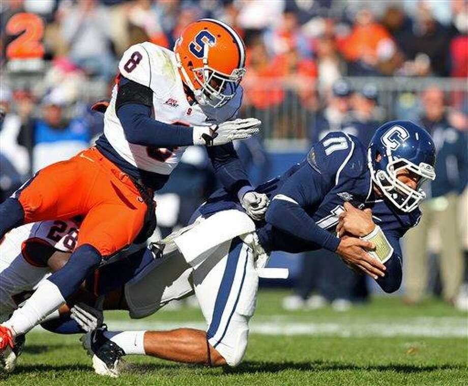 November 5, 2011: Connecticut Huskies quarterback Scott McCummings (11) is tripped up by Syracuse Orange safety Jeremi Wilkes (28) and Syracuse Orange cornerback Keon Lyn (8) during the NCAA football game between Connecticut and Syracuse at Rentschler Field in East Hartford, Connecticut. Connecticut defeated Syracuse 28-21. Anthony Nesmith/CSM (Cal Sport Media via AP Images) Photo: ASSOCIATED PRESS / AP2011