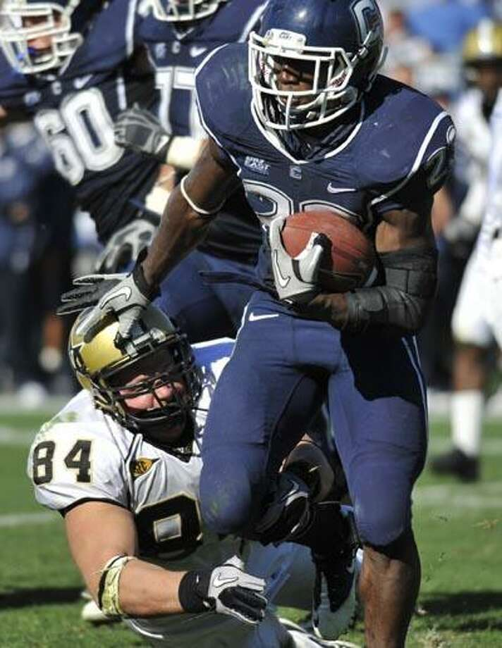 Connecticut's Jordan Todman, right, is tackled by Vanderbilt's Rob Lohr (84) during the second half of an NCAA college football game in East Hartford Saturday. (AP) Photo: ASSOCIATED PRESS / FR125654 AP