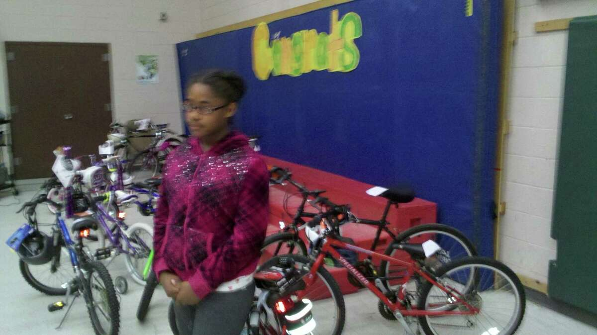 Rochelle Reid, 10, a fifth-grader at Macdonough Elementary School in Middletown, stands with her new bike, complements of Essex-based Bikes for Kids. Reid is the recipient of the organization's 13,000 bike.