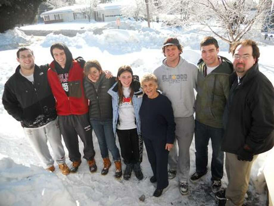 Barbara Douglas photo/Assistant football coach Jeff McDonald (far right)culled together volunteers Nicki Sofmess, Daniel D'Arcy, Bobby Rosenthal, Tim Morley, Hannah Berkman and Ryan Coffey for the dig, part of The Middletown Press's ongoing effort to help city seniors dig out of the snow. Resident Eleanor Skubel is fourth from right.