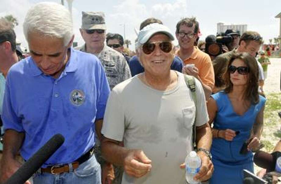 Florida Governor Charlie Crist and entertainer Jimmy Buffett walk along Pensacola Beach,  Fla., on Saturday, June 5, 2010.  Buffett is synonymous with the white-sand beaches along the Gulf Coast that are now being fouled by crude from the massive oil spill. He's planning to open a hotel in Pensacola Beach, Florida, in two weeks.   (AP Photo/Michael Spooneybarger) Photo: ASSOCIATED PRESS / AP2010