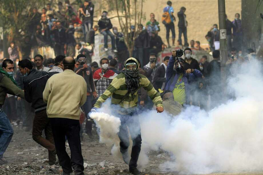 A protester runs to throw a tear gas canister away during clashes with the Egyptian riot police near Tahrir square in Cairo, Egypt, Tuesday. Egypt's civilian Cabinet has offered to resign after three days of violent clashes in many cities between demonstrators and security forces, but the action failed to satisfy protesters deeply frustrated with the new military rulers. (AP Photo/Khalil Hamra) Photo: ASSOCIATED PRESS / AP2011