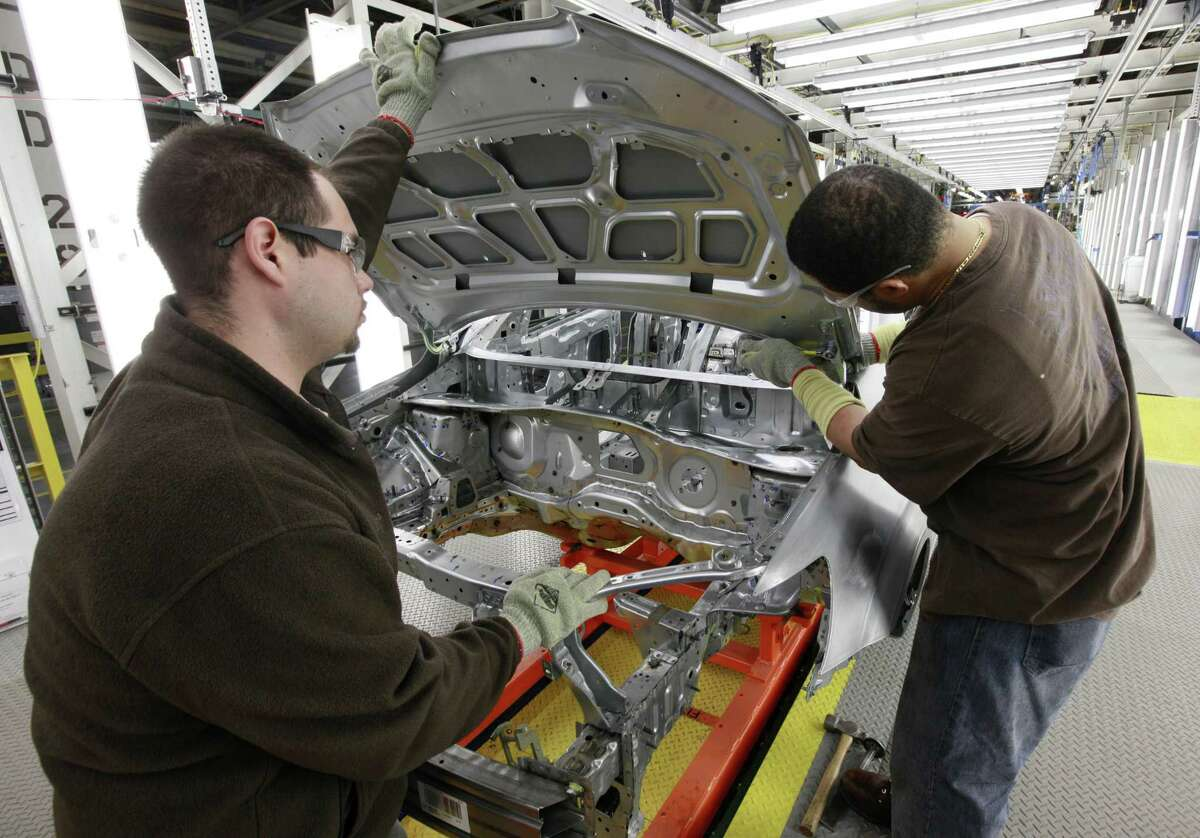 In this May 19 photo, assembly line workers Dave Zamora, left, and Steven Saleem work on a pre-production Chevrolet Sonic at the General Motors Orion Assembly plant in Orion Township, Mich. U.S. manufacturing activity expanded in May at the slowest pace in 20 months, the latest sign that the sharp rise in energy prices is hampering economic growth. (AP Photo/Paul Sancya)
