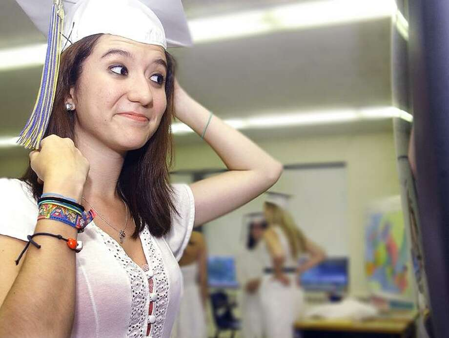 The Middletown Press) Amy-Lynn Vanacore, right, gets a little help from  Gabrielle Valentin personalizing her mortar board -- something that's not allowed at the school -- after she receives her diploma at commencement exercises at Mercy High School Thursday. Vanacore had a roll of duct tape hidden in her dress to stick it on with.