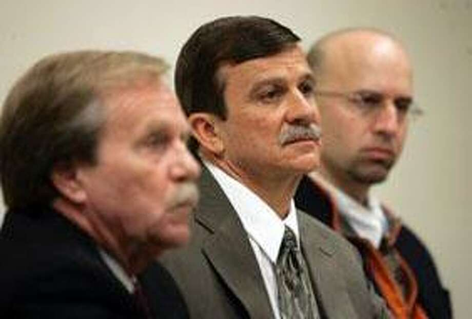 Flanked by his lawyers, Michael Devlin, left, and John Geida, right, David Messenger, center, listens to testimony during his appearance before the Connecticut Psychiatric Security Review Board at Connecticut Valley Hospital in Middletown, Conn., Friday, May 1, 2009. Messenger was acquitted in 2001 of manslaughter by reason of insanity in the bludgeoning death of his wife, Heather, in 1998 and is serving a 20-year sentence at the hospital. (AP Pool Photo/Bob Child, Pool) Photo: AP / Pool AP