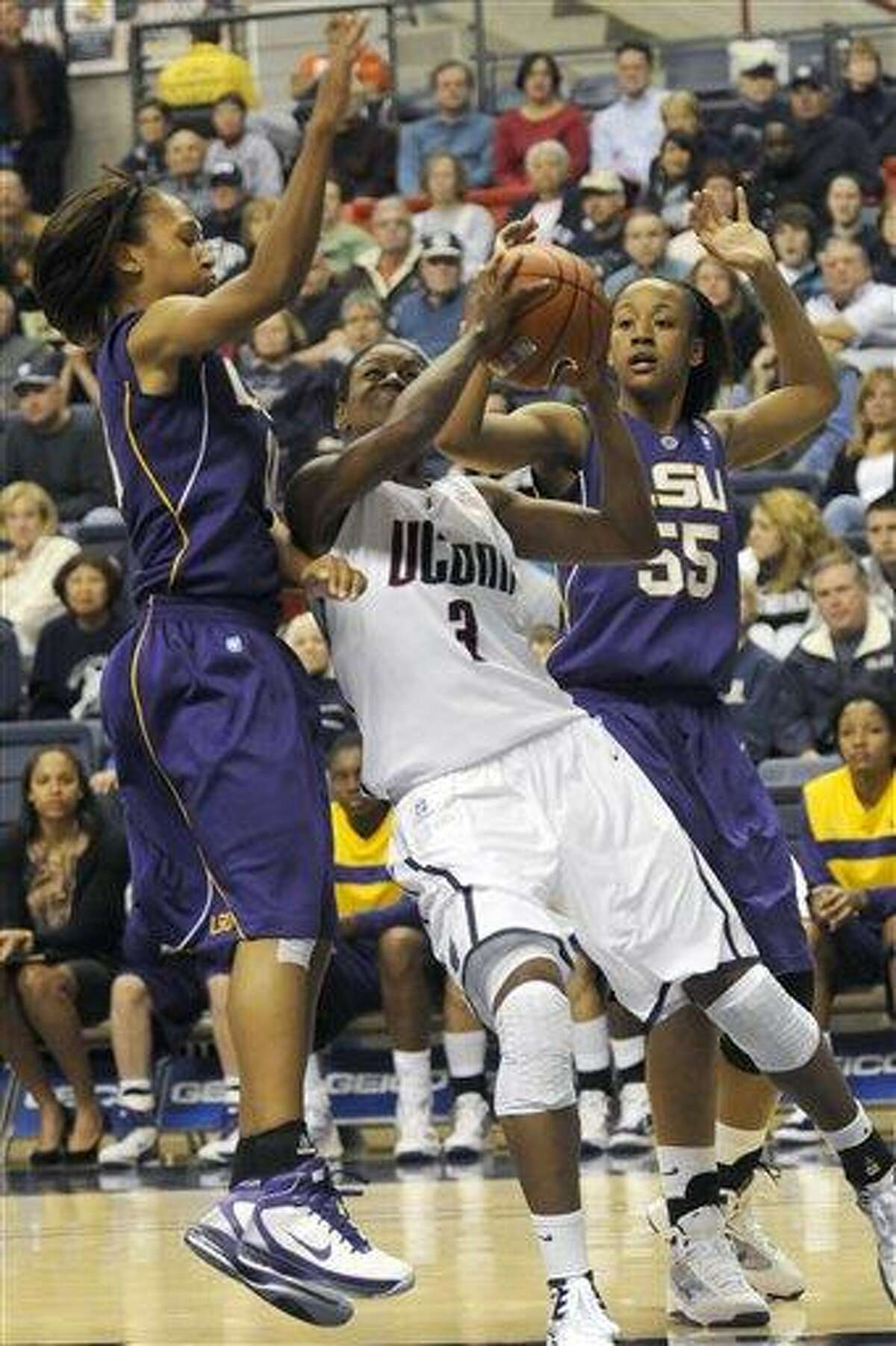 LSU's Adrienne Webb, left, and LaSondra Barrett, right, try to block Connnecticut's Tiffany Hayes as Hayes took a shot in the first half of their NCAA women's basketball game at Storrs, Conn., Sunday, Nov. 28, 2010. (AP Photo/Bob Child)