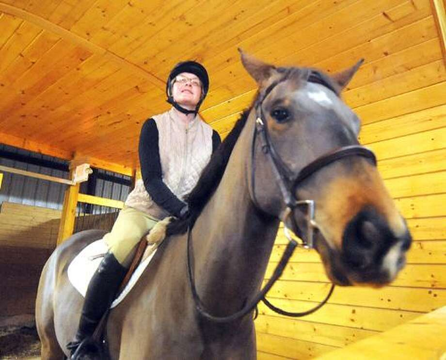 In this photo taken Nov. 22, 2010, Kristen Kuzmickas-Guadagnino, a nationally competitive rider,  looks out at riders inside the 100x200 indoor riding arena,  while sitting on her horse DonStar, at her families  Full Circle Farm in Manchester, Conn. Family farming in this town has nearly vanished over the years, falling victim to commercial and residential development. But up on Birch Mountain, the Zeppa family has found a way to keep the tradition alive, exchanging the cultivation of vegetables and strawberries for the training of horses. (AP Photo/Journal Inquirer, Jim Michaud) Photo: AP / Journal Inquirer