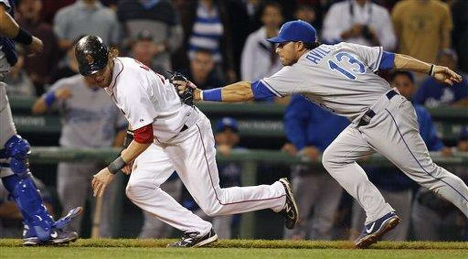 Boston Red Sox Josh Reddick, left, gets caught in a rundown while trying to steal home as Kansas City Royals third baseman Mike Aviles makes the tag in the 12th inning of a baseball game at Fenway Park in Boston, early morning Tuesday, July 26, 2011. (AP Photo/Charles Krupa) Photo: ASSOCIATED PRESS / AP2011