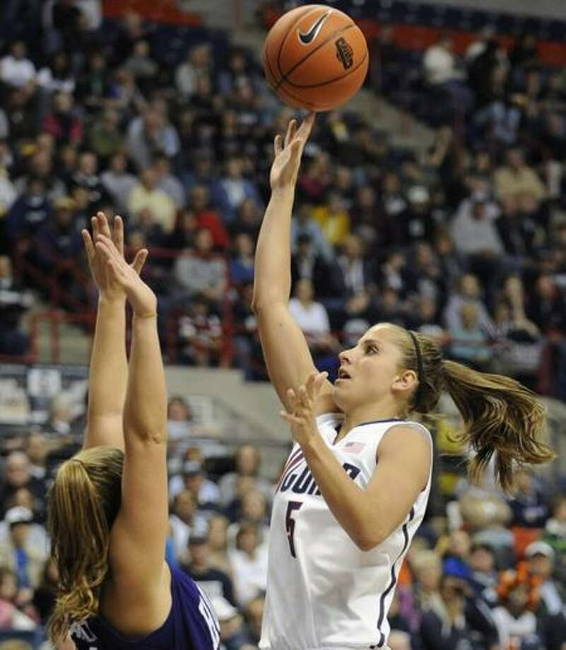 Connecticut's Caroline Doty, right, shoots over Holy Cross' Meredith Ward, left, in the second half of an NCAA women's college basketball game in Storrs, Conn., Sunday, Nov. 13, 2011. Doty, who sat out last season with her third major knee injury, scored nine points and played 22 minutes in her first game back since the 2010 national championship game. (AP Photo/Jessica Hill) Photo: AP / AP2011