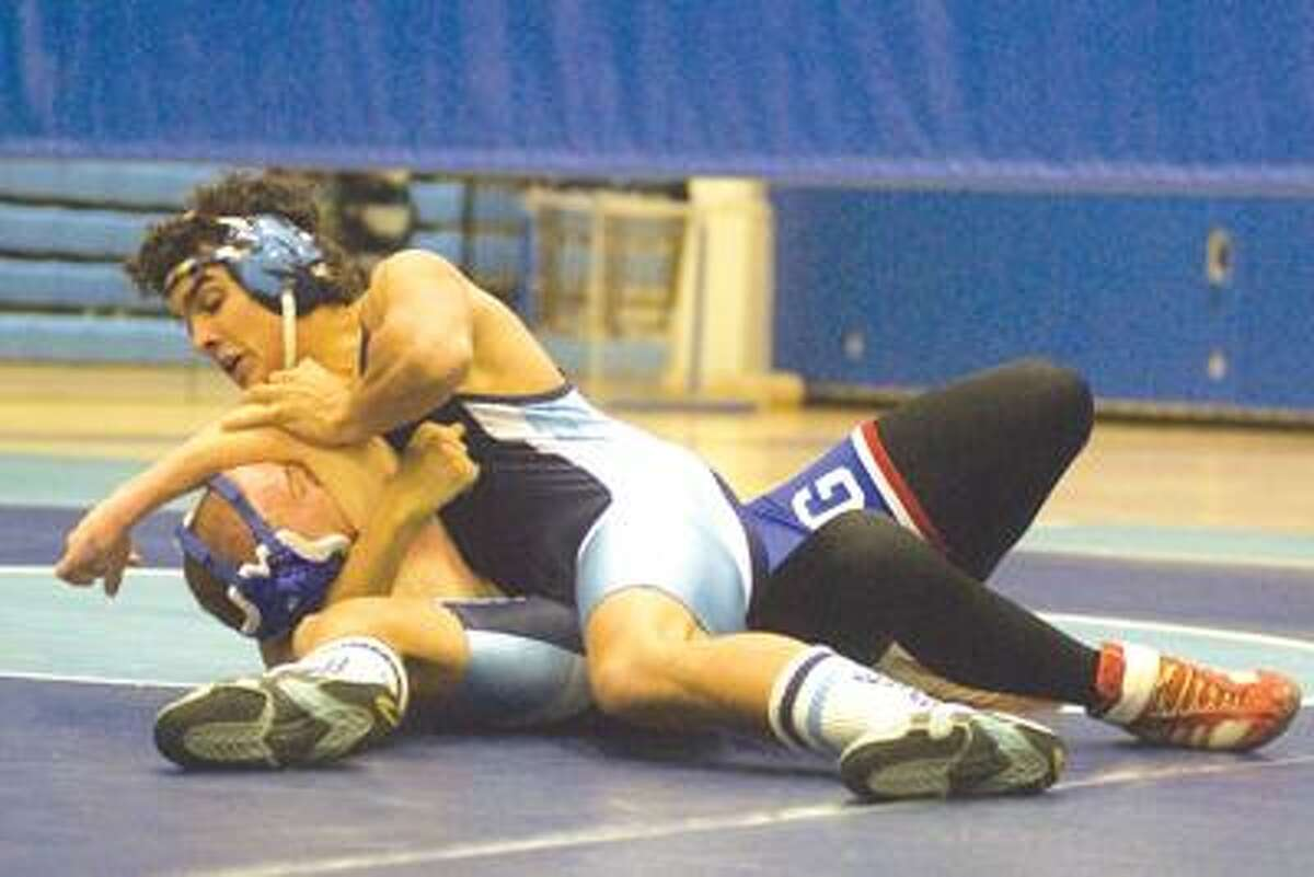 Middletown's Devon Carrillo, Top, wrestles Nick Pucholsky of Glastonbury during a meet in December at Middletown High School. Carrillo won the Class L State Champion in 171 pounds and will pursue a New England championship starting tonight. (Max Steinmetz / Special to the Press)