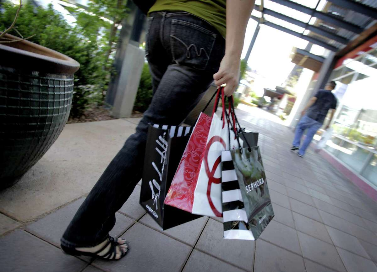 A shopper walks through the outdoor San Tan Village Mall Monday in Gilbert, Ariz. A private research group says soaring prices in gas and other household costs pulled down consumers' confidence in March, after hitting a three-year high in February. (AP Photo/Matt York)