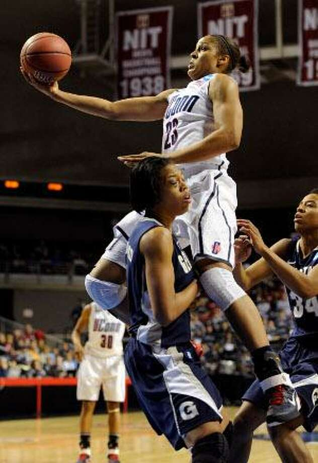 AP  Connecticut forward Maya Moore (23) shoots over Georgetown forward Adria Crawford in the first half of an NCAA tournament regional semifinal on Sunday in Philadelphia. Moore was named as an AP first team All-American