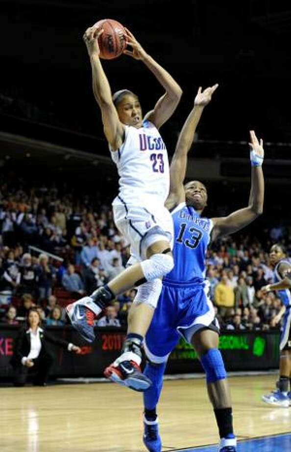 AP  Connecticut forward Maya Moore shoots over Duke guard Karima Christmas in the first half of an NCAA tournament regional final in Philadelphia. The Huskies won 75-40. Moore scored 28 points to reach 3,000 in her career.
