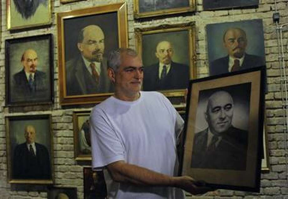 Peter Pinter, owner of the Pinter Gallery, shows a photograph of Hungarian communist leader Matyas Rakosi backdropped by portraits of Soviet revolutionary Vladimir Lenin before their auction in Budapest, Hungary, Monday, Nov. 22, 2010. More than 200 pieces of communist era relics were found by the Hungarian government in various ministries and state warehouses and will be sold in early December to benefit the victims of last month's red sludge disaster. (AP Photo/Bela Szandelszky) Photo: AP / AP