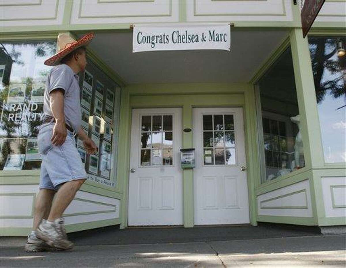 A man walks on East Market Street in Rhinebeck, N.Y., where a sign hangs congratulating Chelsea Clinton and fiance Marc Mezvinsky Wednesday, July 28, 2010. Clinton and Mezvinsky plan to marry in the upstate New York village of Rhinebeck on Saturday. (AP Photo/Mike Groll)