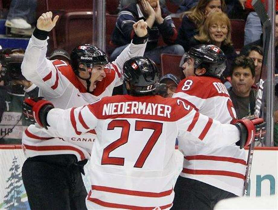 Canada's Sidney Crosby (87) is congratulated by Drew Doughty (8) and Scott Niedermayer (27) after Crosby scored the game-winning goal in the overtime period of a men's gold medal ice hockey game against USA at the Vancouver 2010 Olympics in Vancouver, British Columbia, Sunday, Feb. 28, 2010. (AP Photo/Gene J. Puskar) Photo: AP / AP