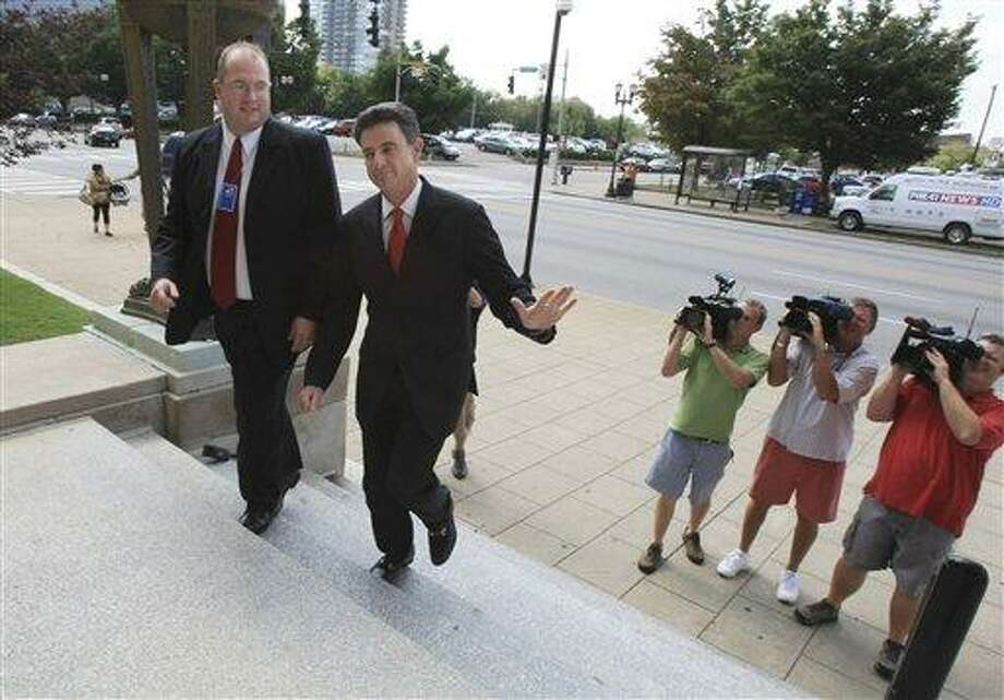 A representative from the US Attorney's Office escorts University of Louisville basketball coach Rick Pitino, second left, to the federal courthouse in Louisvile Wednesday, July 28, 2010.  Pitino will testify in the trial of Karen Sypher who is accused of attempting to extort money from the coach after a sexual encounter.  (AP Photo/ The Courier-Journal, Barry Westerman)  NO MAGS NO SALES NO ARCHIVES Photo: AP / The Courier-Journal