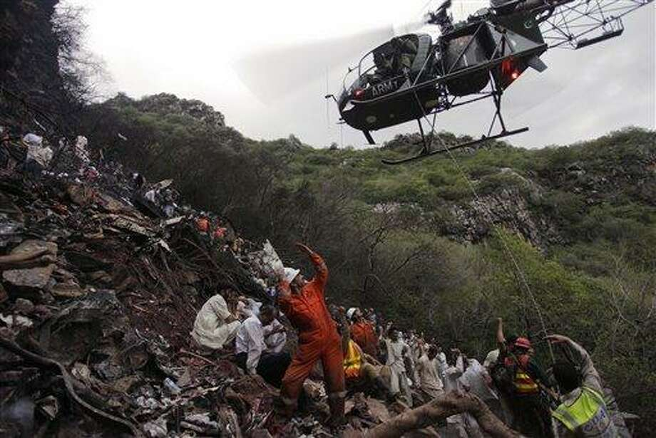 A Pakistan helicopter picks dead bodies from the site of plane crash in Islamabad, Pakistan on Wednesday, July 28, 2010. A government official says all 152 people on board the plane that crashed in the hills surrounding Pakistan's capital were killed. (AP Photo/Mohammad Sajjad) Photo: AP / AP
