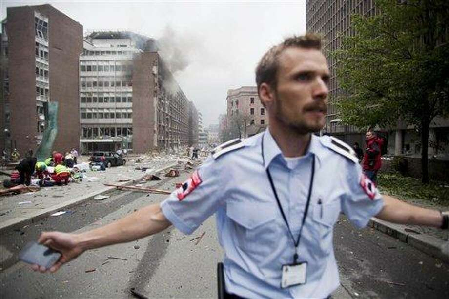 An official attempts to clear away spectators from buildings in the centre of Oslo, Friday July 22, 2010, following an explosion that tore open several buildings including the prime minister's office, shattering windows and covering the street with documents.(AP Photo/Fartein Rudjord) Photo: ASSOCIATED PRESS / AP2011