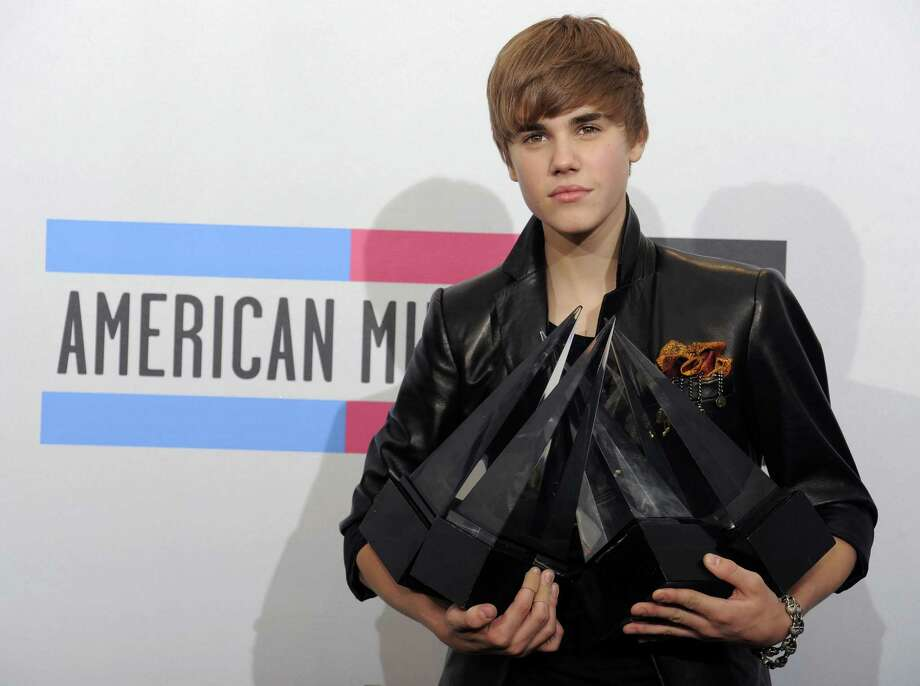 Justin Bieber hold his awards backstage at the 38th Annual American Music Awards on Sunday, Nov. 21, 2010 in Los Angeles. (AP Photo/Chris Pizzello) Photo: AP / AP