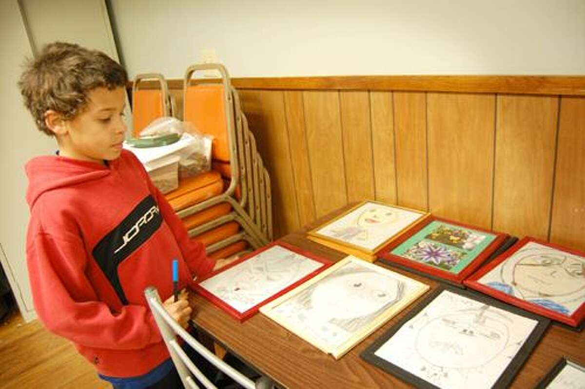 Claire Michalewicz I The Middletown Press Rajah Mueller, 9, shows off some of the drawings he's created for the Homeschoolers Art Gala this evening at the Levi E. Coe Library in Middlefield. Rajah is one of about 30 children who contributed artwork to the annual gala.