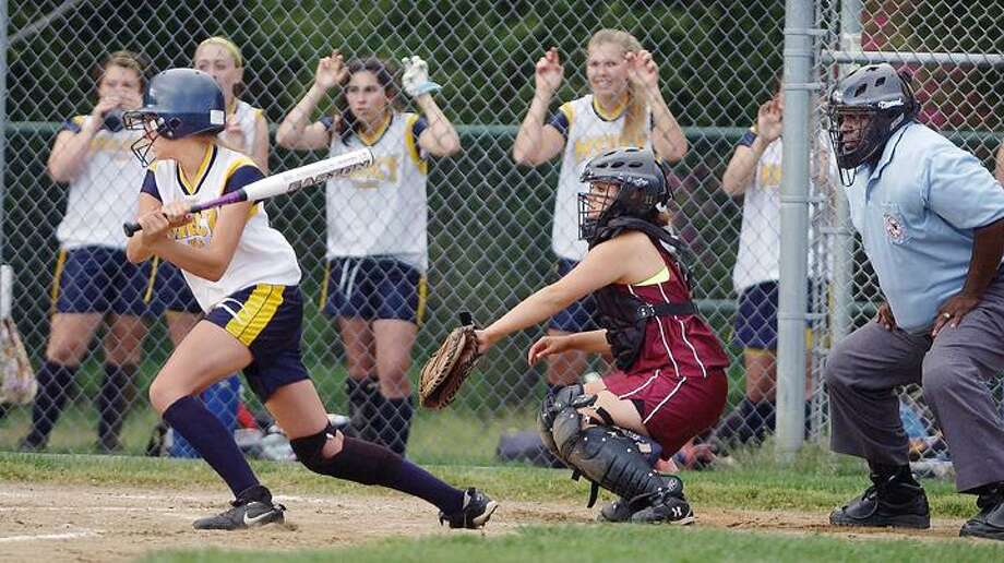Mercy's Ashley Petit follows through on a base hit Friday as North Haven catcher Jess Kiehl looks on from behind the plate in Mercy's 5-2 win. (Catherine Avalone / The Middletown Press)
