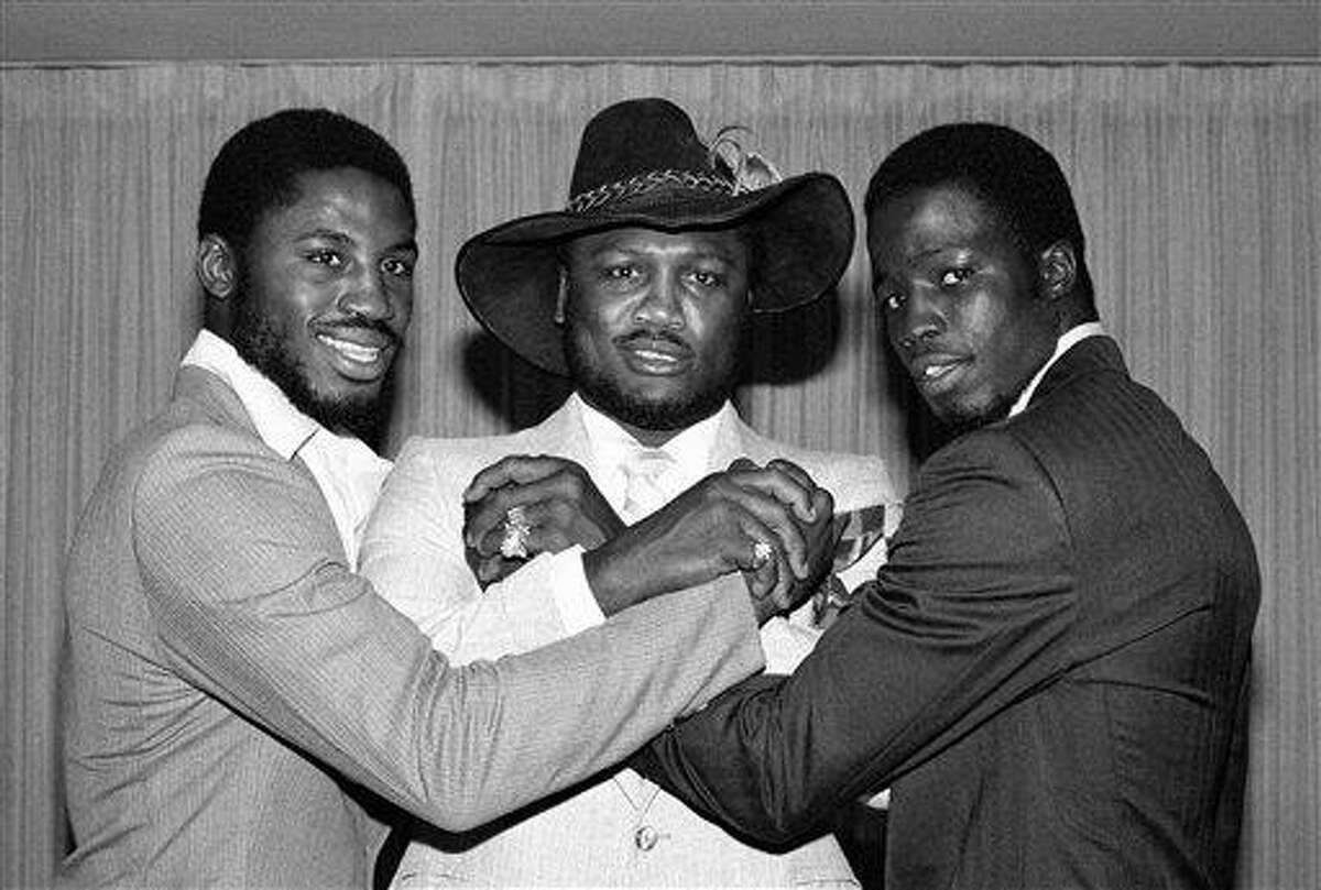 FILE - In this file photo taken Sept. 3, 1980, former heavyweight boxing champion Joe Frazier joins hands with his son Marvis Frazier, left, and James Shuler, right, in New York's Madison Square Garden. Frazier, the former heavyweight champion who handed Muhammad Ali his first defeat yet had to live forever in his shadow, died Monday Nov. 7, 2011 after a brief fight with liver cancer. He was 67. (AP Photo/Ray Howard, File)
