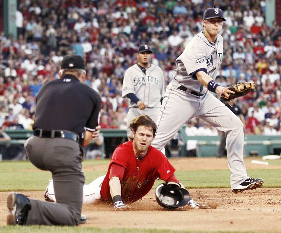 ASSOCIATED PRESS Boston's Josh Reddick slides across first base safely as Seattle Mariners first baseman Justin Smoak looks to the umpire for the call during the second inning of Friday's game at Fenway Park in Boston. The Red Sox won 7-4.