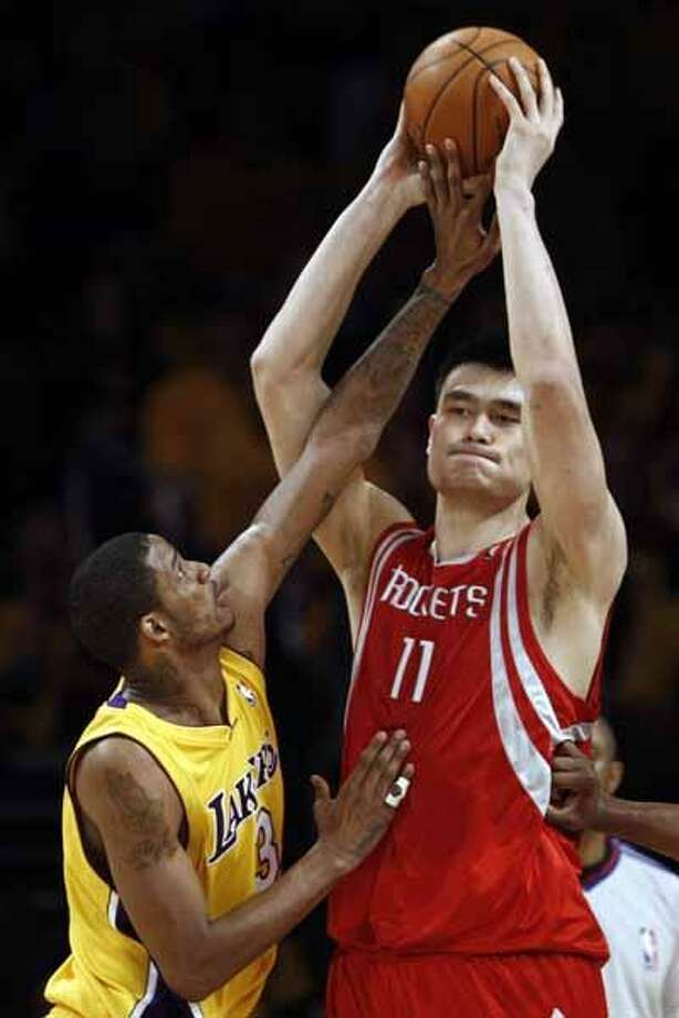his May 4, 2009, file photo shows Houston Rockets' Yao Ming, of China, right, looking to make a pass while being defended by Los Angeles Lakers' Trevor Ariza during the first half of Game 1 of a second-round NBA playoff series, in Los Angeles. A person with knowledge of the decision says All-Star center Yao Ming is returning to the Houston Rockets next season, accepting the player option in his contract. (AP) Photo: AP / AP