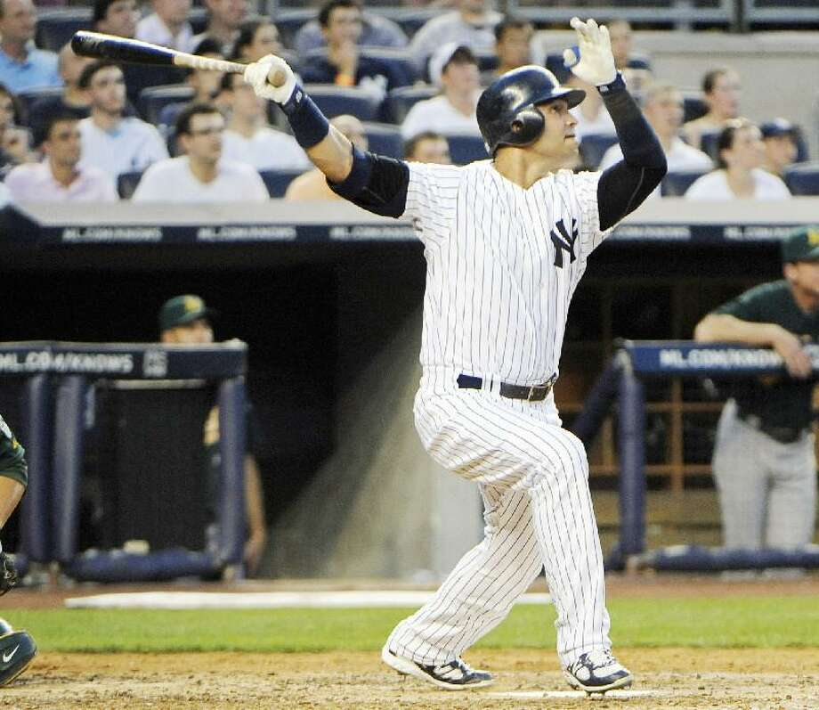 ASSOCIATED PRESS New York Yankees' Nick Swisher hits a two-run home run during the third inning of Friday's game against the Oakland Athletics at Yankee Stadium in New York. The Yankees won 14-7.