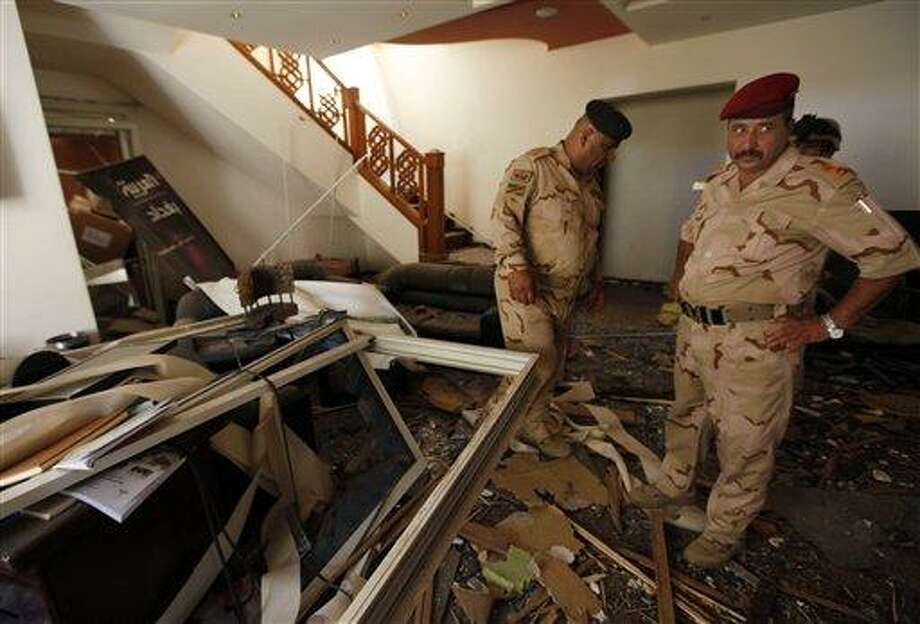 Iraqi army soldiers stand in the ruins of the office of the Al-Arabiya television station after a suicide bomber driving a minibus struck in Baghdad, Iraq, Monday, July 26, 2010. The bomber was apparently waved through the first checkpoint at the Al-Arabiya television station after security guards checked his identification, said Iraqi military spokesman Maj. Gen. Qassim al-Moussawi. The blast killed and injured several people at the popular Arabic-language satellite news channel early Monday. (AP Photo/Hadi Mizban) Photo: AP / AP