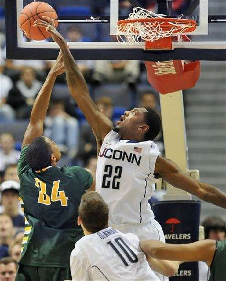 Connecticut's Roscoe Smith (22) blocks a shot by C.W. Post's Charles McCann in the second half of an NCAA college basketball exhibition game in Hartford, Conn., Sunday, Nov. 6, 2011.  Connecticut won 91-61. (AP Photo/Jessica Hill) Photo: AP / AP2011