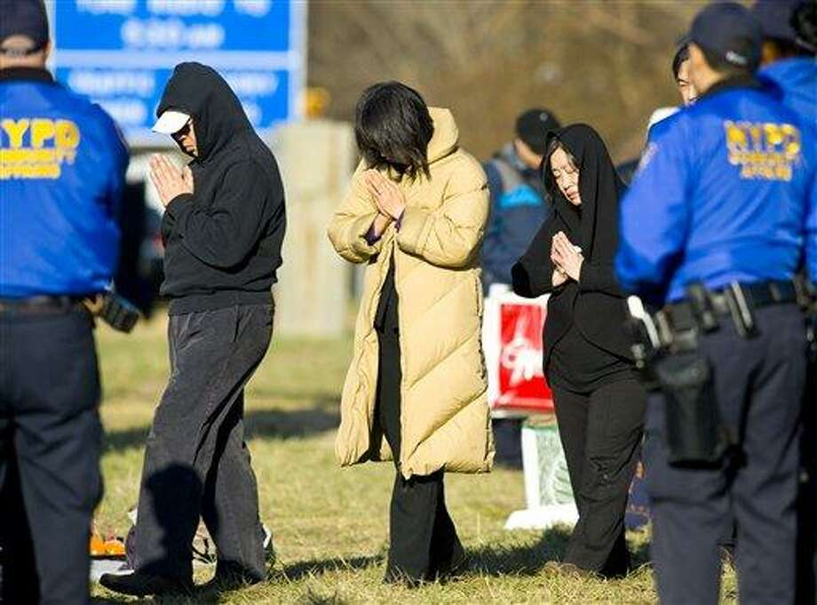 Victim's family members participate in a Buddhist service at the location of a tour bus crash that left fifteen people dead, Saturday, March 19, 2011 in the Bronx borough of New York. Fifteen people were killed March 12, when the bus returning to New York from Connecticut overturned and was split in two by a sign support pole. (AP Photo/Stephen Chernin) Photo: ASSOCIATED PRESS / AP2011