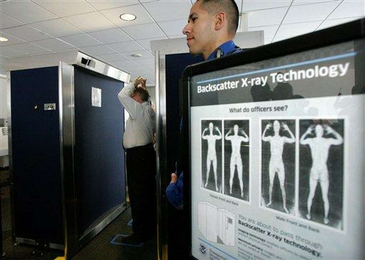 In this photo taken Sept. 1, 2010, Transportation Security Administration employee Anthony Brock, left, demonstrates a new full-body scanner at San Diego's Lindbergh Field, with TSA employee Andres Lozano in San Diego. The American Civil Liberties Union has denounced the machines as a