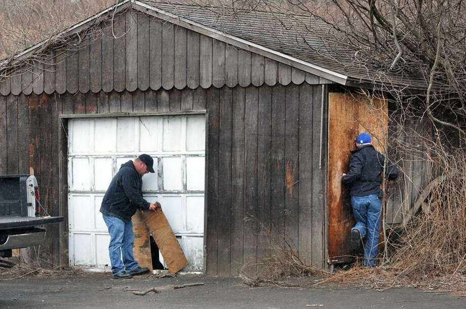 Orange--Contractors Joe Aniballi, left and Tom Capecelatro board up the old farm stand at the corner of Indian River Rd. and Prindle Avenue, where missing Orange teen Isabella Oleschuk was found hiding since Sunday morning. Photo by Peter Casolino/New Haven Register03/23/11 Cas110323