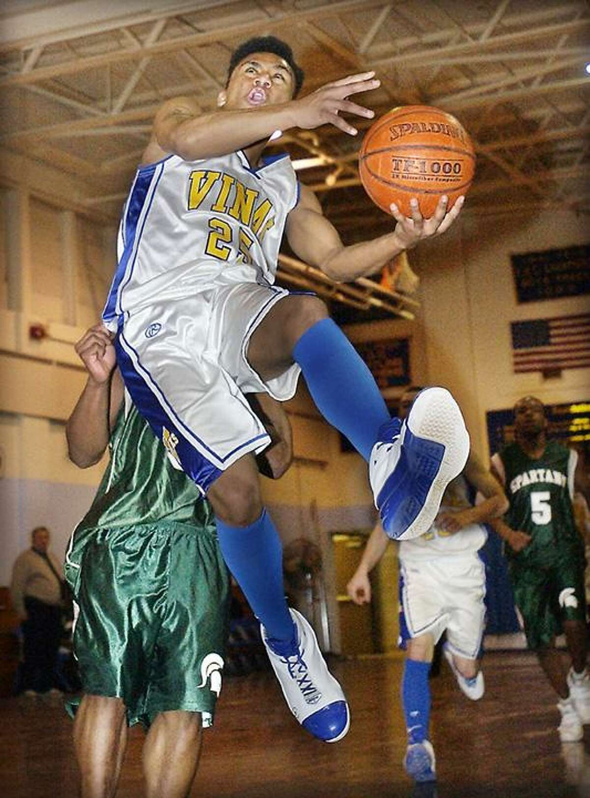 FILE PHOTO - Vinal's Lawrence Young goes up for a shot against Stamford Academy defender Juan Peralta during a home court game in 2009.