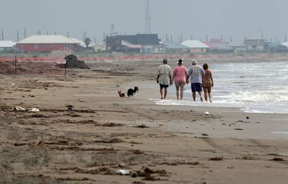 People walk along the surf along the beach in Grand Isle, La., as Tropical Depression Bonnie approaches the coast Saturday, July 24, 2010. Some ships prepared to move back to the site of BP's broken oil well Saturday as the remnants of a weakening Tropical Storm Bonnie rolled into the Gulf of Mexico. (AP Photo/Dave Martin)