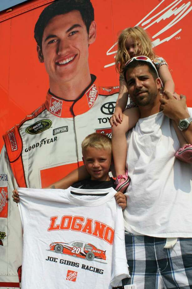 Portland's Jim Tierney, left, shows the Ciesinsk brothers (left-to-right) Aidan, Declan and Ronan some classic racecar photographs at the Joey Logano merchandise trailer in Portland Tuesday afternoon.