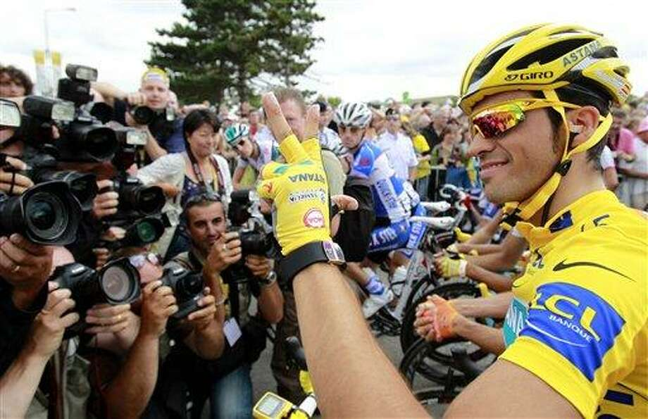 Alberto Contador of Spain, wearing the overall leader's yellow jersey, gestures to indicate his impending 3rd Tour de France victory, before the 20th and last stage of the Tour de France cycling race over 102.5 kilometers (63.7 miles) with start in Longjumeau and finish in Paris, France, Sunday, July 25, 2010. (AP Photo/Bas Czerwinski) Photo: AP / AP