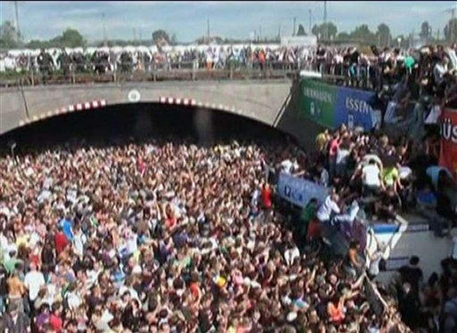"""In this image taken from amateur video people are caught in a stampede by a tunnel entrance as others climb to escape the crush  at this year's techno-music festival """"Loveparade 2010"""" in Duisburg, Germany, on Saturday, July 24, 2010. More than a dozen people were killed and hundreds were injured in a panicked crush of partygoers in an overcrowded tunnel that served as the sole entrance to a German festival billed as the world's largest techno music party. (AP Photo /  <a href=""""http://BILD.DE"""">BILD.DE</a> via APTN) ** TV OUT GERMANY OUT ONLINE OUT NO ARCHIVE USAGE FOR 4 WEEKS ONLY ** Photo: AP / BILD.DE"""