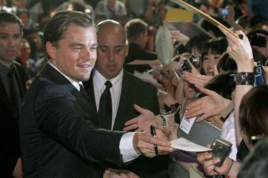 "U.S. actor Leonardo DiCaprio, left, hands over a slip of paper to a fan after giving his autograph on it during the Japan premiere of his sci-fi thriller ""Inception"" in Tokyo, Japan, Tuesday, July 20, 2010. (AP Photo/Shizuo Kambayashi) Photo: AP / AP"