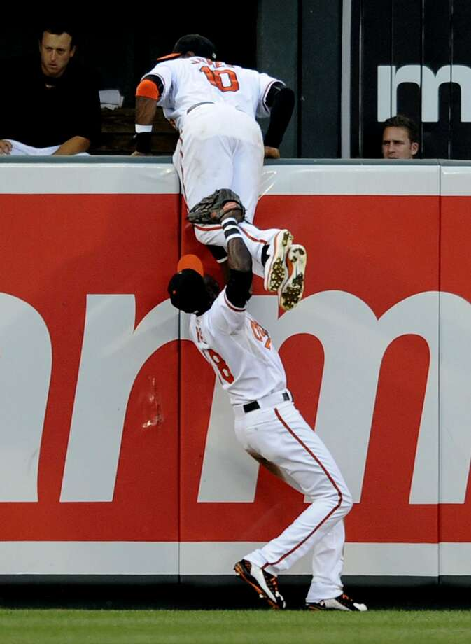Baltimore Orioles left fielder Felix Pie (18) comes to the aid of Adam Jones, top, after Jones leapt in vain for a home run hit by Boston Red Sox's Jarrod Saltalamacchia during the third inning of a baseball game, Monday, July 18, 2011, in Baltimore. (AP Photo/Nick Wass) Photo: ASSOCIATED PRESS / AP2011
